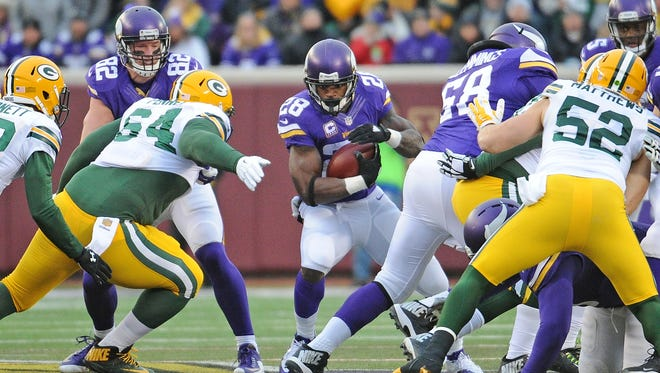 Green Bay Packers defensive end Mike Pennel (64) tries to close a hole in the line as Minnesota Vikings running back Adrian Peterson (28) bursts through at TCF Bank Stadium in Minneapolis.