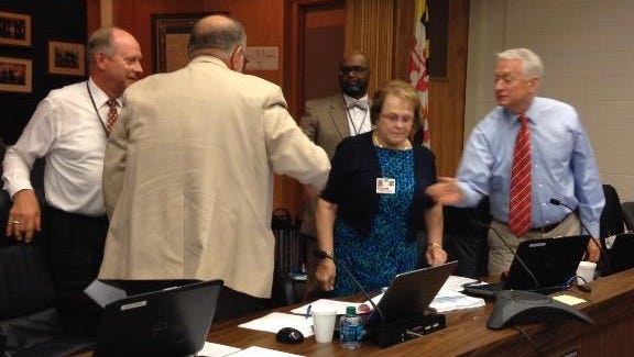 Wicomico County Board of Education President Don Fitzgerald is congratulated by fellow board members Tyrone Chase, Carolyn Elmore and Joseph Ollinger at his right and Superintendent John Fredericksen at his left.