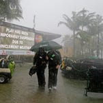 A television crew heads to the clubhouse for cover due to heavy rains and lightning as the third round of the Honda Classic golf tournament is postponed on Saturday.
