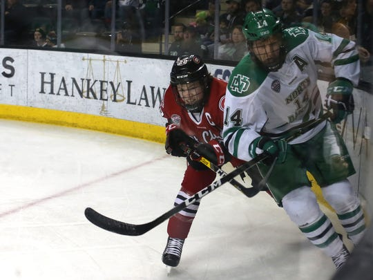 St. Cloud State defensemen Jimmy Schuldt (22) and University of North Dakota forward Austin Poganski (14) chase the puck around the boards in the first period of a NCHC Quarterfinals game between the Fighting Hawks and Huskies, March 10, 2017 at the Ralph Engelstad Arena in Grand Forks, N.D.