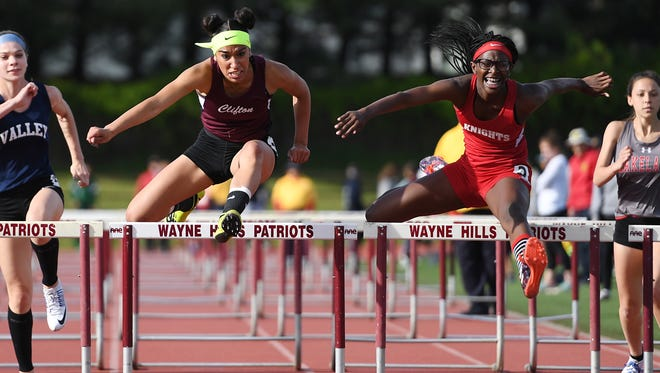 Second day of Passaic County Track championships at Wayne Hills High School on Wednesday, May 10 2017.  At left, Alenys Morales, of Clifton, on her way to finishing first in the 100M Hurdles. At right, Benae Johnson, of JFK, on her way to finishing second.