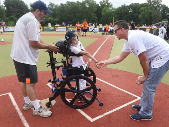 Detroit Tigers catcher James McCann greets J.T. Lozon of St. Clair Shores with a handshake as he crosses home plate at the Baseball Fantasy Camp for Kids Saturday. J.T. was assisted by his father, Tom.