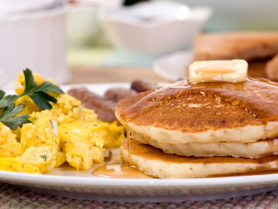A hearty breakfast plate with pancakes, eggs and sausages.