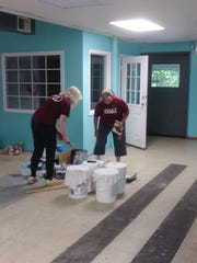 Volunteers from BB&T paint the interior of the Pickens