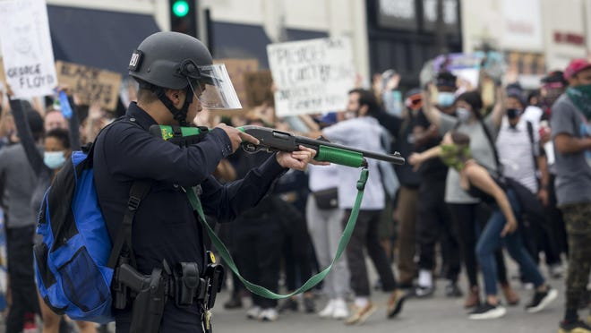 FILE - In this May 30, 2020, file photo, a police officer prepares to fire rubber bullets during a protest over the death of George Floyd in Los Angeles. Attorney General Xavier Becerra on Monday, June 15, 2020, called for California to create a way to end the law enforcement careers of police officers who engage in serious misconduct, along with other changes in tactics and training in the wake of weeks of national protests over police brutality.