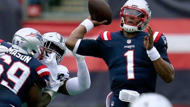 New England Patriots quarterback Cam Newton (1) passes under pressure in the first half of an NFL football game against the Las Vegas Raiders, Sunday, Sept. 27, 2020, in Foxborough, Mass.