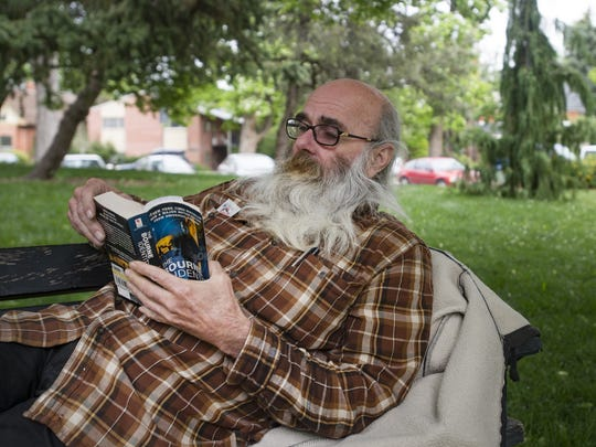Melvin Swett relaxes with a book in the shade outside of Old Town Library on Tuesday, June 13, 2017.