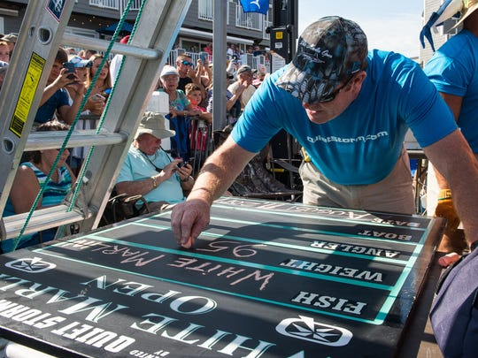 A White Marlin Open staff member writes info for the first place fish brought in by the crew of the Wire Nut of Ocean City on Friday, Aug. 11, 2017. The 95.5 pound marlin is the third largest in the tournament's history.