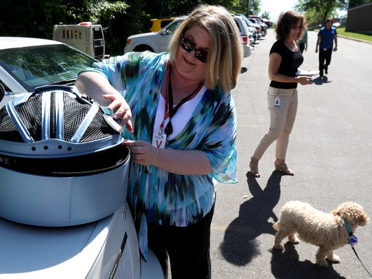 Lindsey Wolko the CEO and Chairman of the Center for Pet Safety in Washington D.C. works on zipping up a sleepy pod soft crate that can be buckled into the back seat of a car.