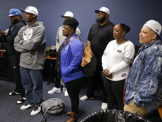 Malik Hooker's family watches as he speaks to the media.