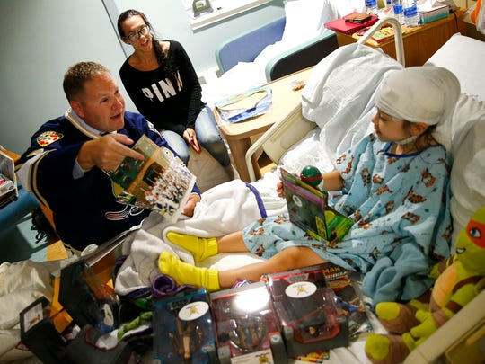 New Jersey State Policemen's Benevolent Association Hockey team member Michael Schulze presents a team picture along with toys to K. Hovnanian Children's Hospital patient Anthony Ruzzo, 4, Farmingdale, Monday, August 7, 2017.  Schulze is Monmouth County Sheriff's officer and was making the delivery along with 'Daniela's Wish.'  Anthony mother Maeghan Struck is also shown.