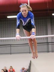 Farmington United's Kelly Shrosbree performs on uneven parallel bars during the Canton Invitational.