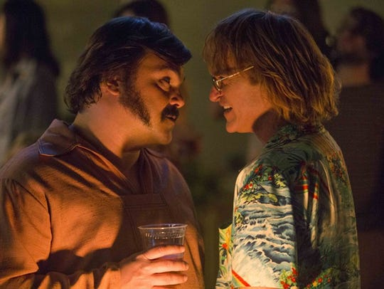 Jack Black, left, and Joaquin Phoenix play drinking