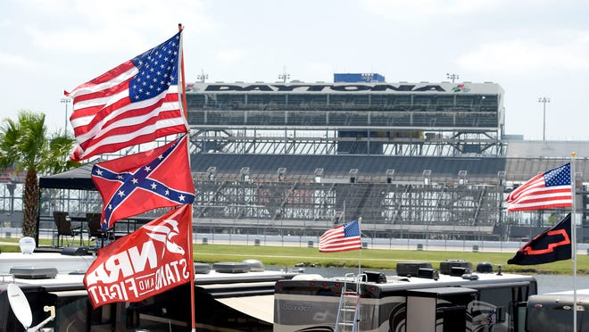 FILE - In this July 4, 2015, file photo, confederate and American flags fly on top of motor homes at Daytona International Speedway in Daytona Beach, Fla. Bubba Wallace, the only African-American driver in the top tier of NASCAR, calls for a ban on the Confederate flag in the sport that is deeply rooted in the South.