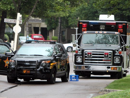 Law enforcement and fire department vehicles block a road at the Orchard of Landen apartment complex.