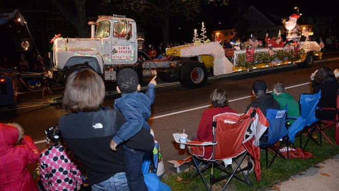 Spectators enjoy a float during last year's Millville Christmas Parade. This year's parade will be held at 7 p.m. Nov. 25 on High Street.