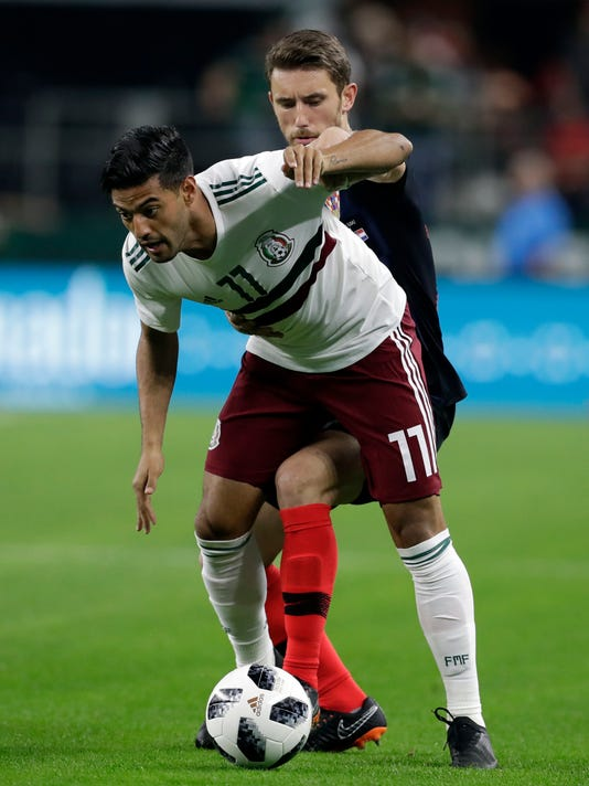 CORRECTS DATE OF PHOTO  - Mexico forward Carlos Vela, front, and Croatia forward Josip Pivaric, rear, compete for control of the ball in the first half of a friendly soccer match in Arlington, Texas, Tuesday, March 27, 2018. (AP Photo/Tony Gutierrez)