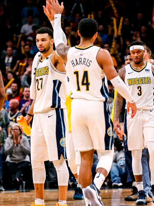 Denver Nuggets guard Jamal Murray (27) high-fives Gary Harris (14) in the final minute of play against the Portland Trail Blazers during the fourth quarter of an NBA basketball game, Monday, April 9, 2018, in Denver. Denver beat Portland 88-82. (AP Photo/Jack Dempsey)