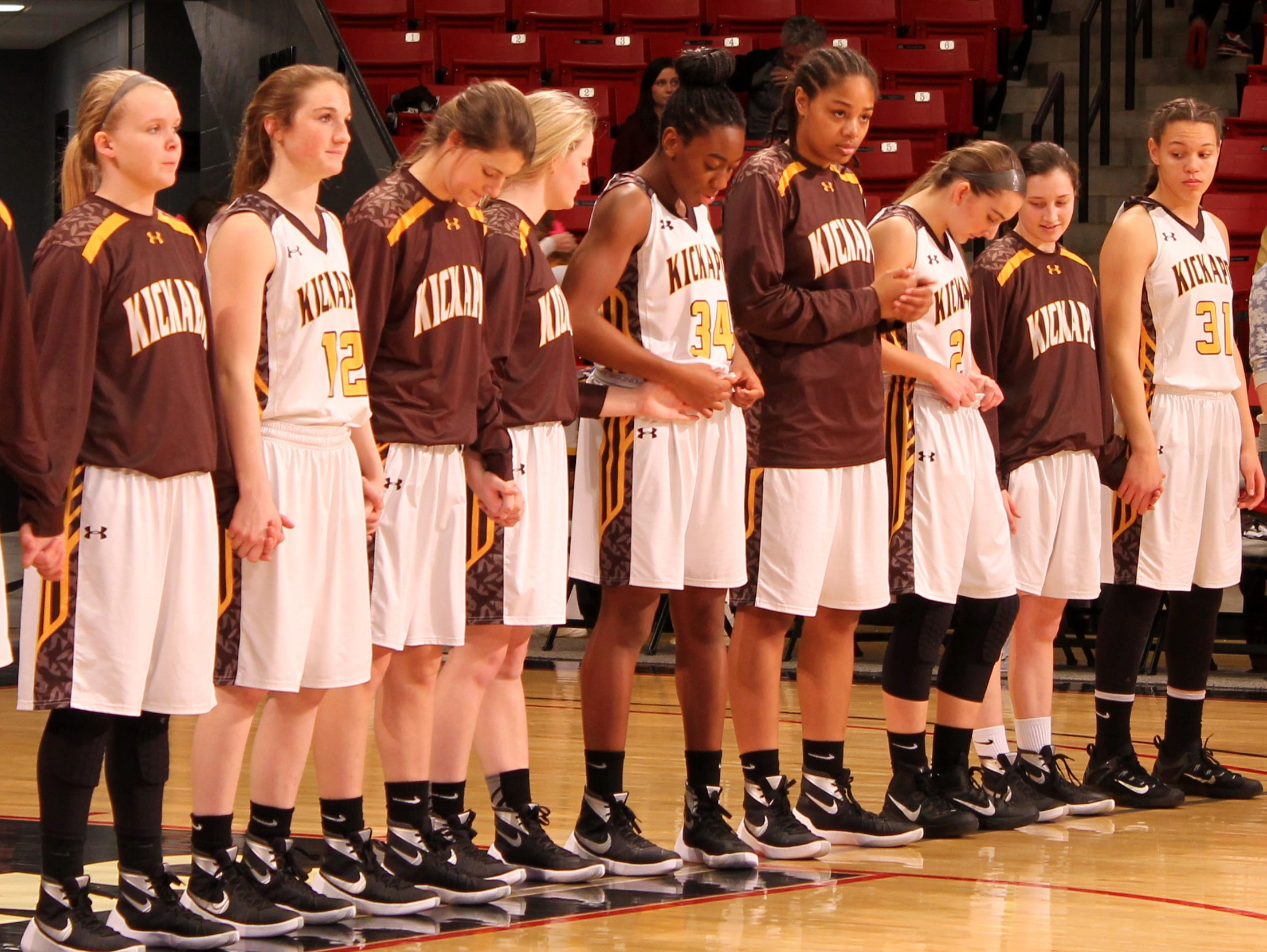 Kickapoo High School's girls basketball team stands together moments before the national anthem prior to a game against Strafford in the Pink and White Lady Classic.