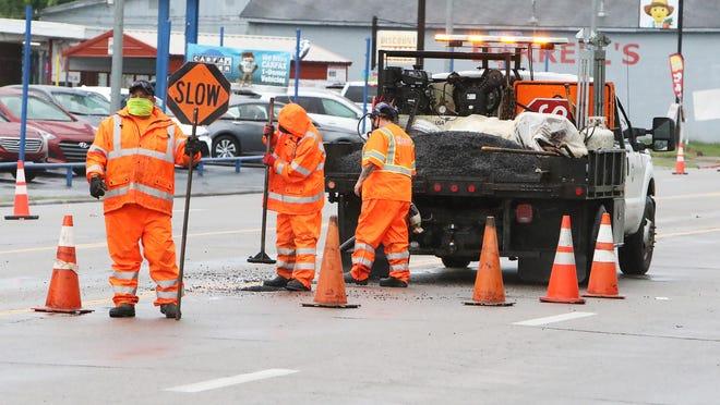 An ARDOT maintenance crew repairs potholes along Midland Boulevard in the rain, Monday, August 31, 2020.