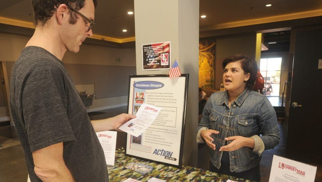 Brenda Perez, right, the Christmas Shoppe coordinator for Area Christians Taking Initiative on Needs, talks to Brian Pederson about the shops in the lobby of the Reality Church in 2015.