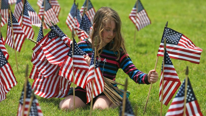 Eight-year-old Julia Stock carries an armful of American flags as she helps plant them to fill fill in the letter S on the Great Lawn at the Waterfront Saturday.  The flags -- 15,000 of them -- were planted to spell USA and to honor veterans.