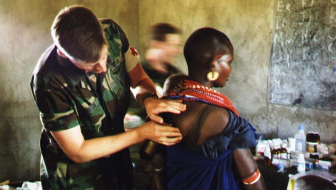 A younger Dr. Jeff Johnson serving in Africa measures a lipoma on a patient's back.