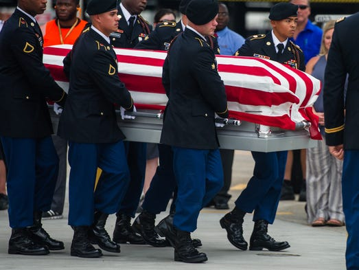 Military personnel carry the remains of U.S. Army Sgt.