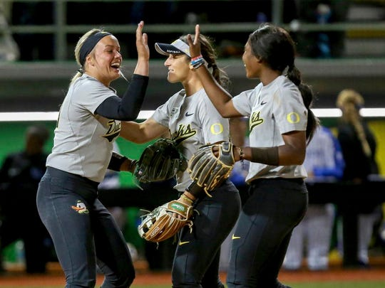 Oregon's Miranda Elish, Lauren Lindvall and DJ Sander, from left, celebrate Oregon's win over Kentucky in an NCAA softball tournament super regional game Friday, May 25, 2018, in Eugene, Ore. (Collin Andrew/The Register-Guard via AP)