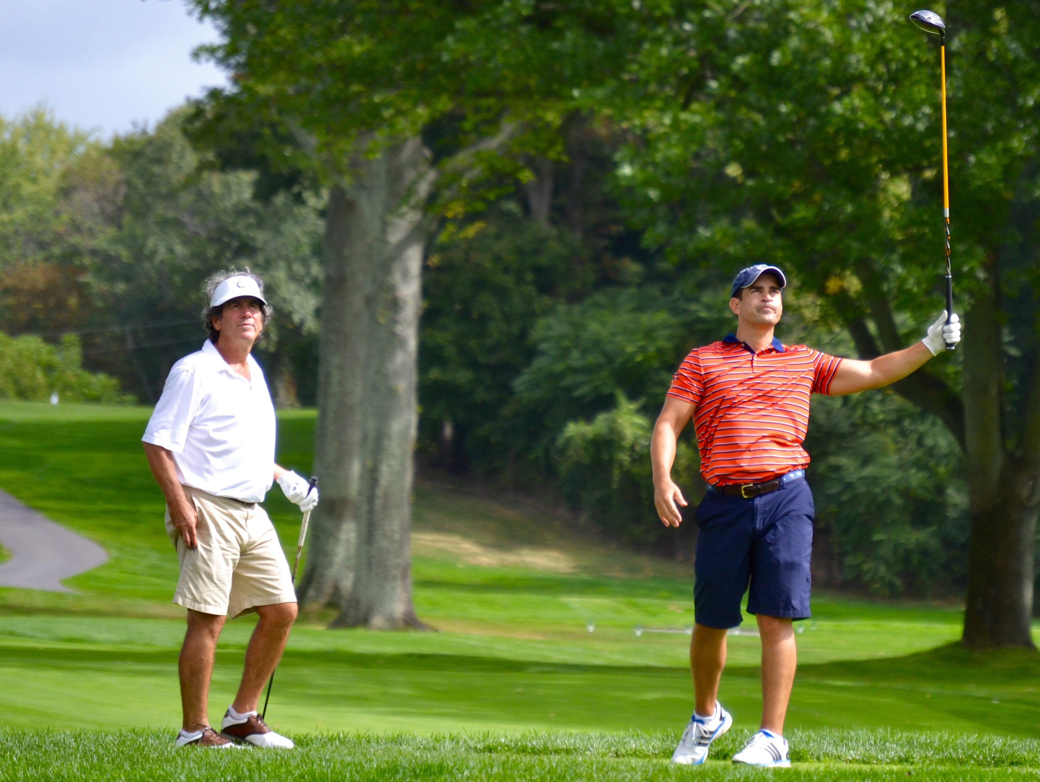 Michael Karger (right) watches his drive fade into the rough alongside the 18th hole at Nassau Country Club Tuesday while John Ervasti looks on.