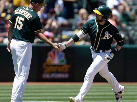 Oakland Athletics' Jed Lowrie, right, is congratulated by third base coach Steve Scarsone (15) after hitting a home run off Cleveland Indians' Dan Otero in the third inning of a baseball game Sunday, July 16, 2017, in Oakland, Calif. (AP Photo/Ben Margot)