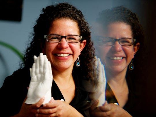 Margarita Smith, owner of Casting the Human Form, poses with one of the casts at her home in Louisville, Tennessee on Tuesday, December 5, 2017. Casting the Human Form uses plaster to create body cast statues.