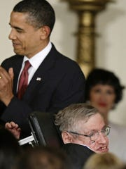 FILE - In this Wednesday, Aug. 12, 2009 file photo President Barack Obama applauds after presenting the 2009 Presidential Medal of Freedom to Stephen Hawking, the renown theoretical physicist and Cambridge University professor, during ceremonies at the White House in Washington. Hawking, whose brilliant mind ranged across time and space though his body was paralyzed by disease, has died, a family spokesman said early Wednesday, March 14, 2018. (AP Photo/J. Scott Applewhite, File)