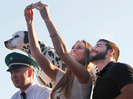 Haley Nabors, center, and Vincent Sawchuk pose for a selfie next to Budweiser Clydesdales driver Will Kurtz and Brewer the Dalmatian Wednesday at the Bell Tower Shops.