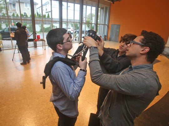 Sean Weiner, right, a member of the faculty at the Jacob Burns Film Center Media Arts Lab in Pleasantville, helps Matthew McLoughlin, 16, of Irvington, left, and J.D. Brown, 17, of Pleasantville, mount a camera on a shoulder brace Oct. 22, 2014. The students are taking part in a six-week short film production class Oct. 22, 2014. The class is a collaborative experience that focuses on producing an original student-generated short film.