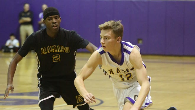 Clarkstown North's Nick Ovchinnikoff (12) pushes the ball down the court with Ramapo's Michael Denis (2) guarding him during boys basketball game at Clarkstown North in New City Jan. 20,  2017.