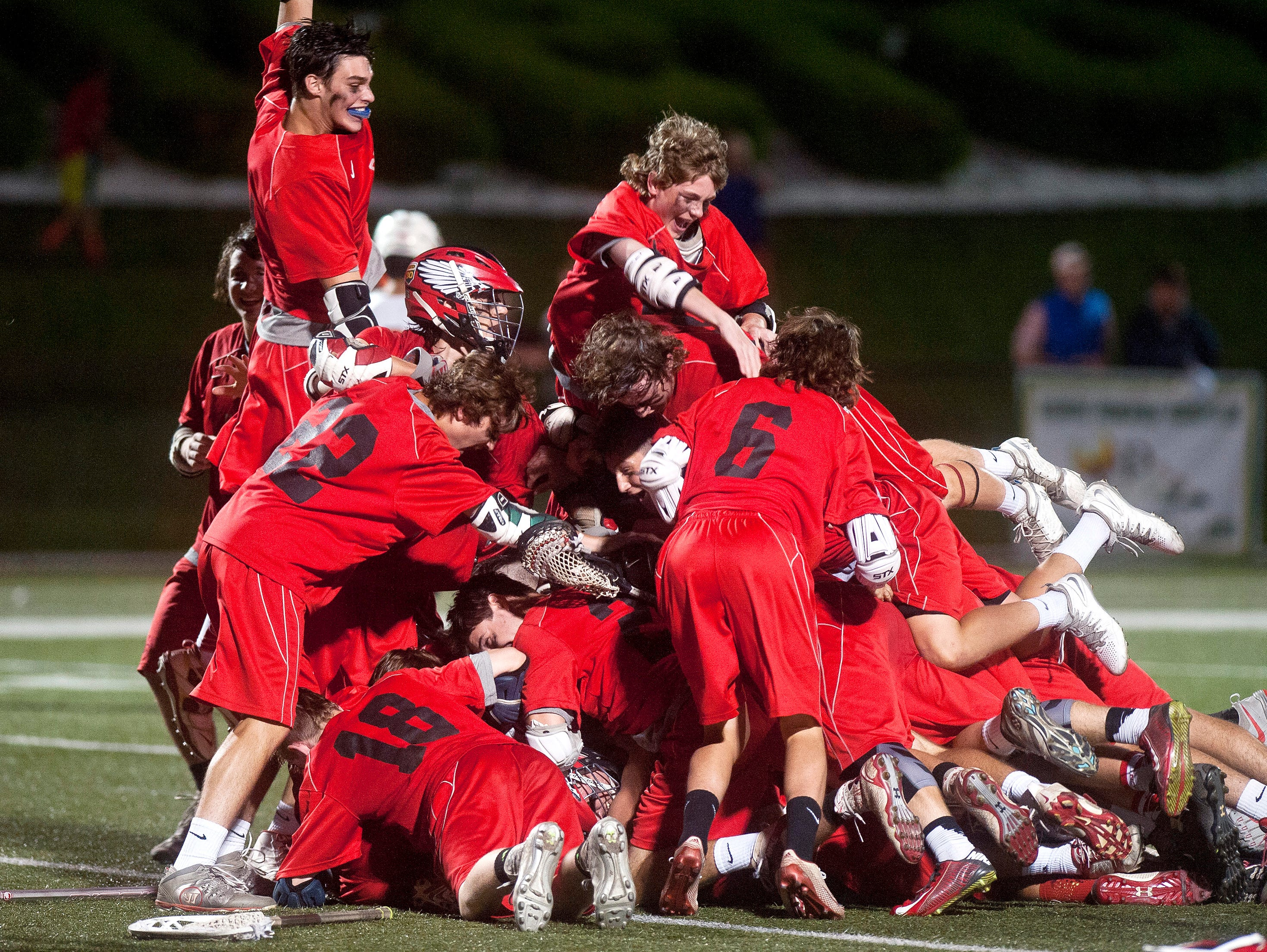 Champlain Valley players leap into a celebratory pile after their 11-10 victory over Middlebury in the Division I boys lacrosse championship game Thursday night at Castleton State College.