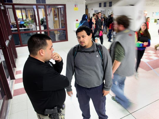 Ignacio Enriquez Jr., a school resource officer at Appleton North High School, stops in the hallway to talk with Manny Miramontes Friday, Dec. 11, 2015, in Appleton, Wis. Enriquez has been a school resource officer at Appleton North since March 2012.