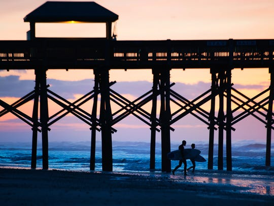 Surfers head out to the ocean from Folly Beach before