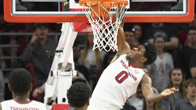 Arkansas guard Jaylen Barford goes up for a dunk over Texas A&M defenders during the second half of an NCAA college basketball game Saturday, Feb. 17, 2018, in Fayetteville, Ark. (AP Photo/Michael Woods)