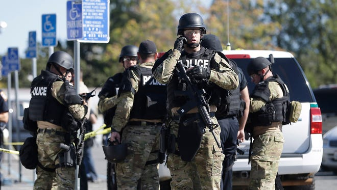 Law enforcement officers dressed in tactical gear prepare to aid in the search of an assailant in Auburn, Calif., who shot three sheriff's deputies in two Northern California counties Friday.