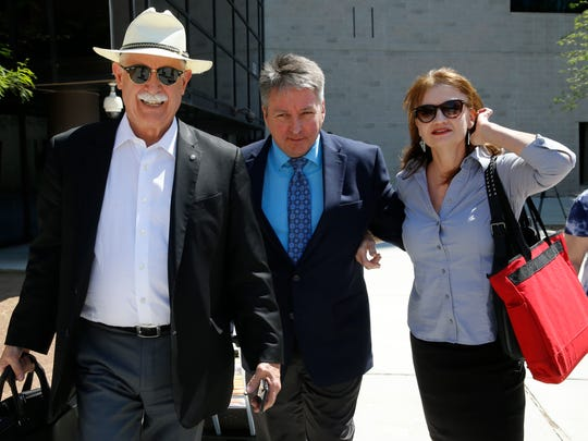 Thomas W. Mills Jr., left, who was representing John Tanner, walks with his client and Tanner's wife recently after exiting the Federal Courthouse after a mistrial was declared in the trial.