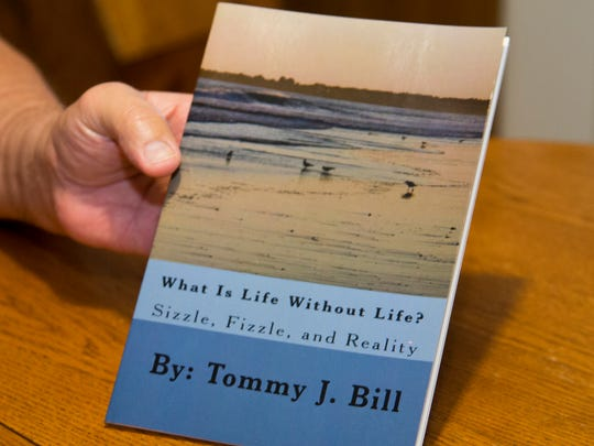 """Tom Bill shows a book of poems he wrote while battling breast cancer at his home near Oxford. Dealing with a disease that has been dubbed a """"women's fight,"""" is difficult. """"It's very emotional,"""" he said. """"It deals with something most people associate with women."""""""