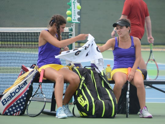 Wylie's Kaitlyn Hathorn, left, hands doubles partner Analeah Elias a towel in between games of a match against a pair from Amarillo Tascosa on the final day of the AISD Invitational Team Tournament on Saturday in Abilene.