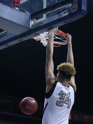 Oskaloosa's Xavier Foster dunks the ball during the