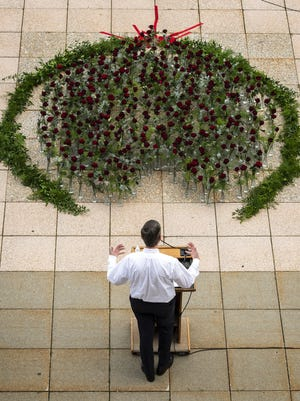 City Manager Edward M. Augustus Jr. speaks during the city's weekly COVID-19 briefing outside City Hall on Thursday in front of roses arranged in a heart to commemorate the 296 Worcester residents who have died from the virus.