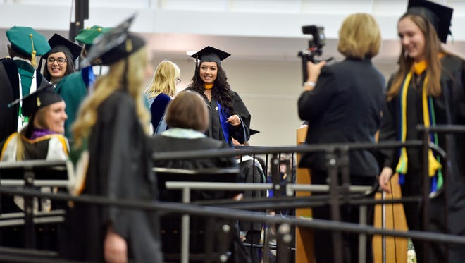 Graduates walk across and off the dais during York College's winter commencement ceremony Wednesday, Dec. 20, 2017, at the Grumbacher Sport and Fitness Center in Spring Garden Township. About 225 students received their degrees, according to Mary Dolheimer, the college's assistant vice president of communications.