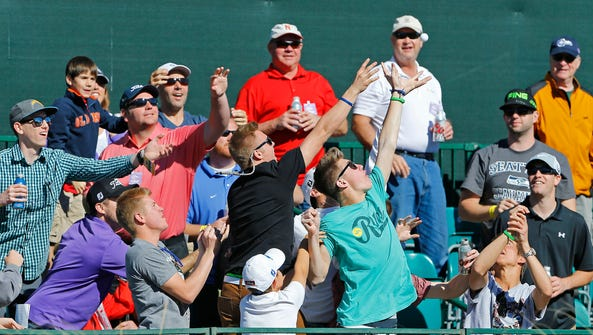 Fans reach for a ball thrown into the stands by Mark
