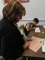 Amy Buelow, an instructional support and Reading Recovery teacher jots down notes in a running record as she works with first-grader Jaeden Solomon to get him up to speed with his peers.