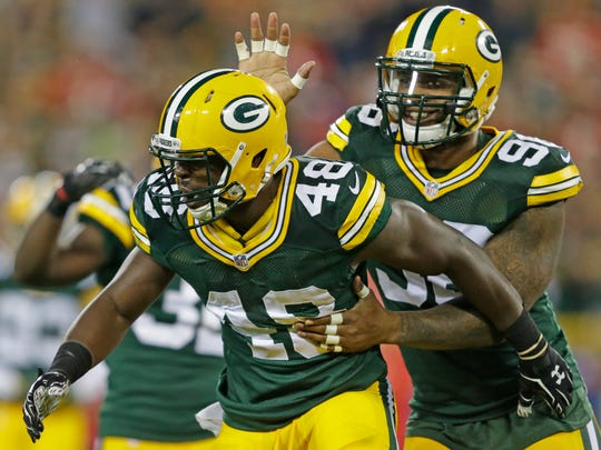 Packers linebacker Joe Thomas (48) celebrates an open field tackle with Mike Neal (96) against the Kansas City Chiefs at Lambeau Field.